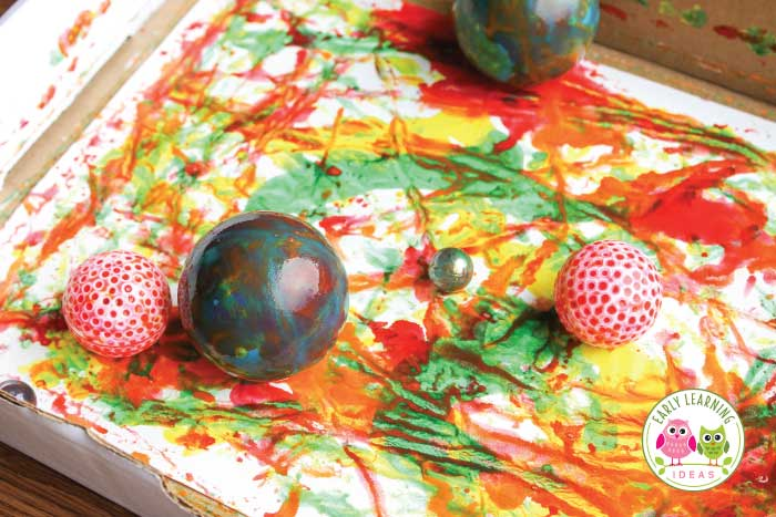 See how art for preschoolers is combined with science when you paint with marbles and balls.  Kids will have fun creating and experimenting with this simple activity. These are great process art ideas for preschool and pre-k. Add the activity to your preschool STEAM, art centers or lesson plans. It's easy to adapt for any season.. spring, summer, fall or winter. Add different balls to increase learning... great science and art activities for your creative curriculum unit on balls or ball theme