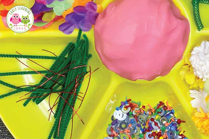 Create a fun flower playdough tray for your kids with these unique material ideas. Your kids will love this open-ended, flower-themed activity. Material and easy ideas for a playdough invitation to play for your flower theme, garden theme or spring theme unit or lesson plans. Add playdough mats for literacy and math learning. Perfect for your preschool or pre-k classroom and fine motor learning centers. Your kids will have fun making flower-themed creations. #preschool #playdough #finemotor
