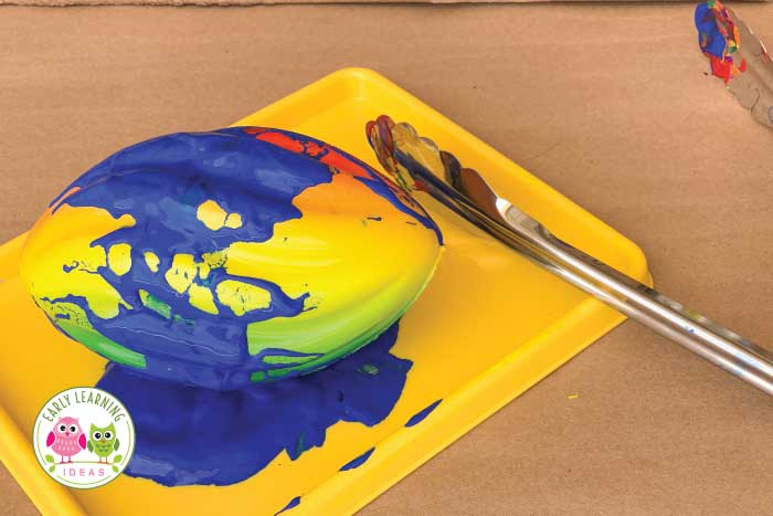 Painting with balls and marbles is a fun way to combine process art and science.  Kids will have fun creating and experimenting with this simple activity. These are great process art ideas for preschool and pre-k. Add the activity to your preschool STEAM, art centers or lesson plans. It's easy to adapt for any season.. spring, summer, fall or winter. Add different balls and a ramp to increase learning...great science and art activities for your creative curriculum unit on balls or ball theme