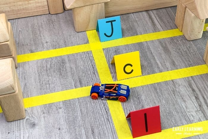 Play based letter recognition activities with letter signs, masking tape, and toy cars