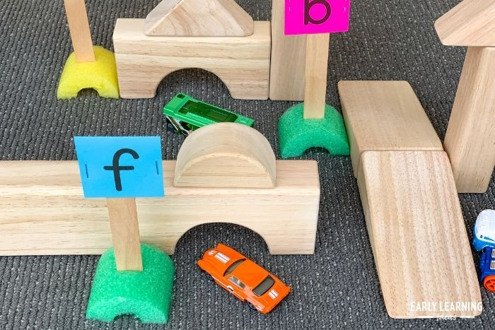 letter recognition activities with letter signs, matchbox cars, and blocks